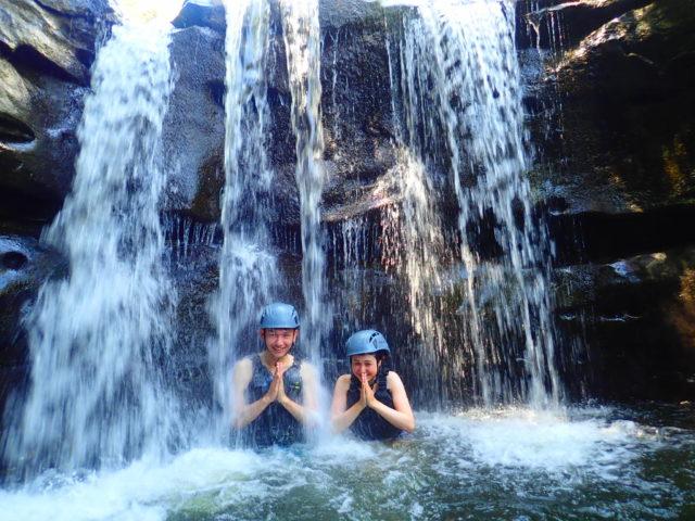 西表島のキャニオニングツアーで滝に打たれる